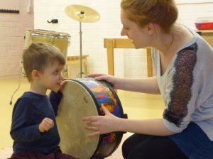Music therapist with child listening to a drum