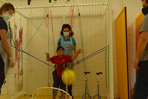 Boy playing football in physiotherapy