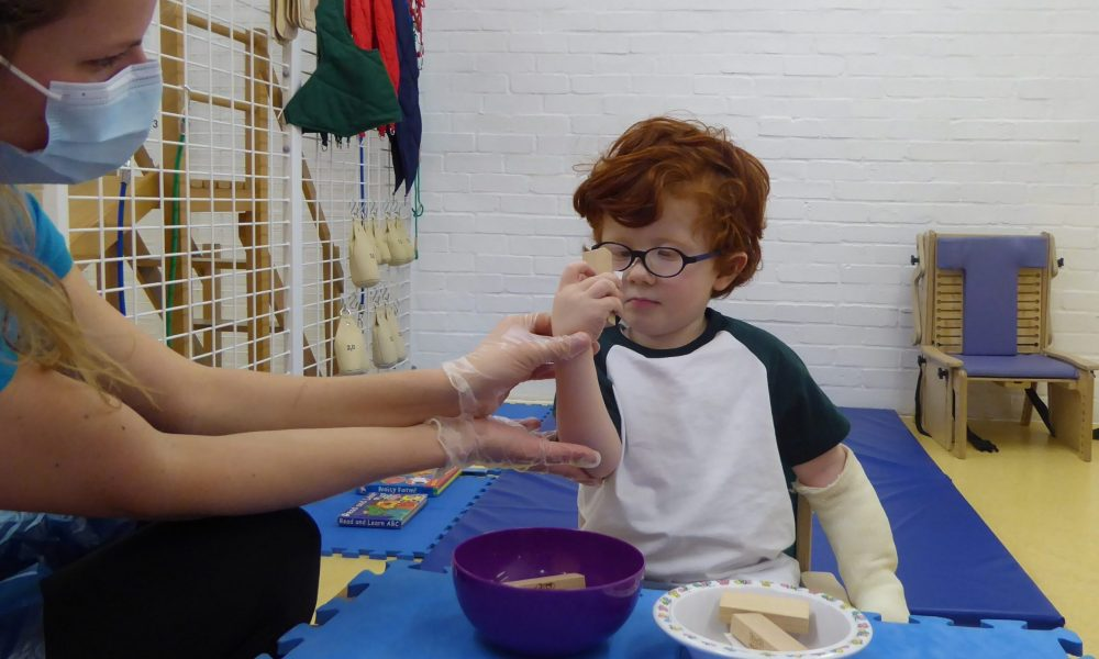 Boy and therapist in CIMT session
