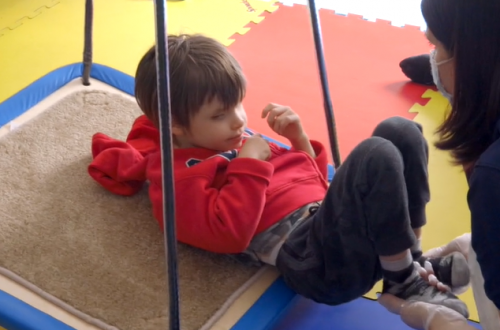 Boy on sensory swing in occupational therapy